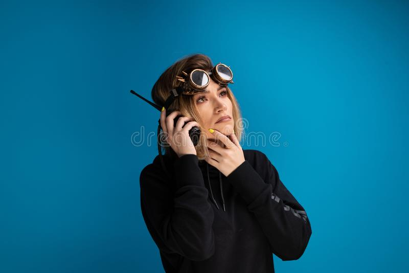 Steam punk girl wearing glasses uses a walkie talkie and poses as thinking while holding her hand close to the mouth stock photo