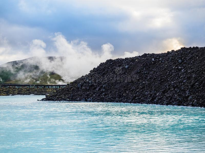 A Portion of the Blue Lagoon, Iceland. Steam rises behind a bed of lava rock at the geothermal springs of the Blue Lagoon near Reykjavik, Iceland stock photos