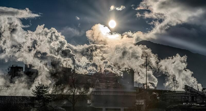 Steam from smokestacks in factory royalty free stock photography