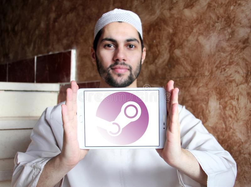 Steam games software company logo. Logo of Steam software company on samsung tablet holded by arab muslim man. Steam is a digital distribution platform developed stock images