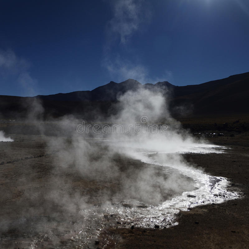 Steam with sun reflection on the water in El Tatio Chile. (Andes mountains royalty free stock image