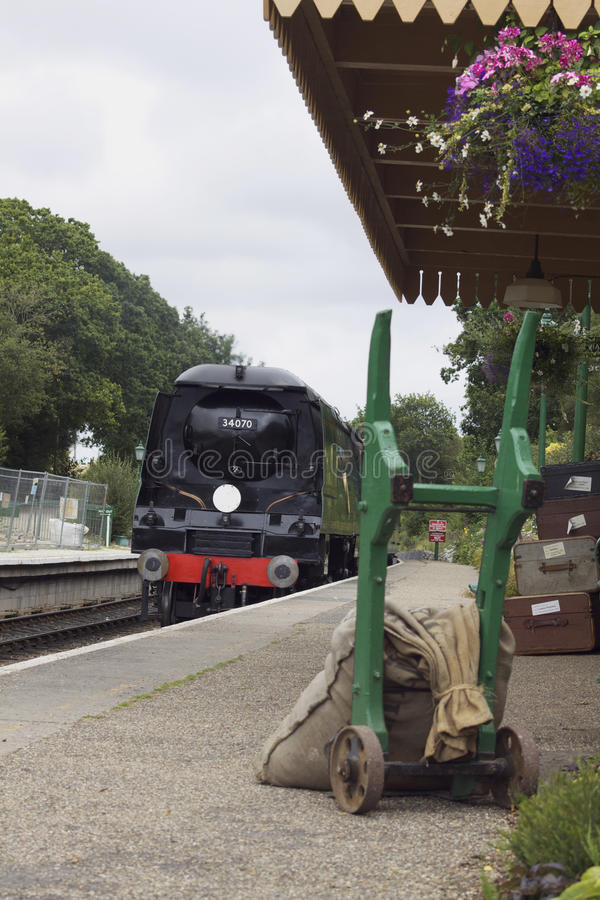 Steam Train. A steam train arriving at Harmans Cross station, part of the Swanage Steam Railway system in Dorset. A platform trolly holding a hessian sack is royalty free stock images