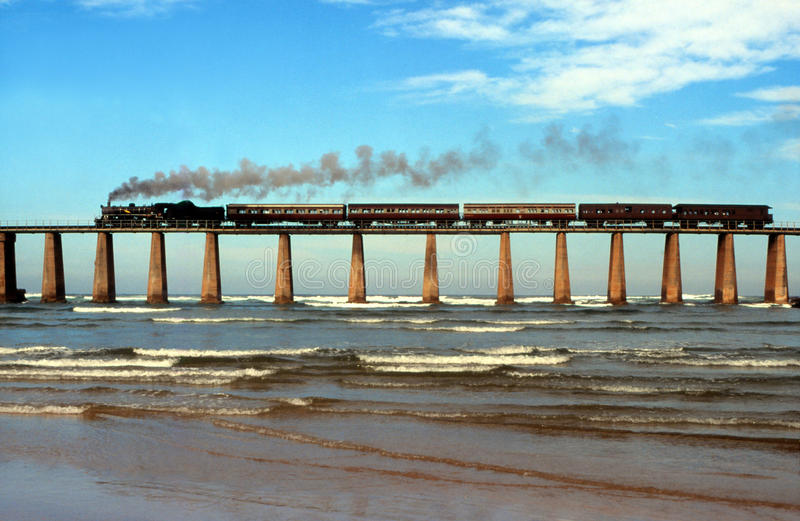 Steam train crossing Kaaimans River bridge South Africa. Former Outeniqua Choo-Tjoe crossing Kaaimans River Mouth on incoming tide at Wilderness on way to Garden royalty free stock images