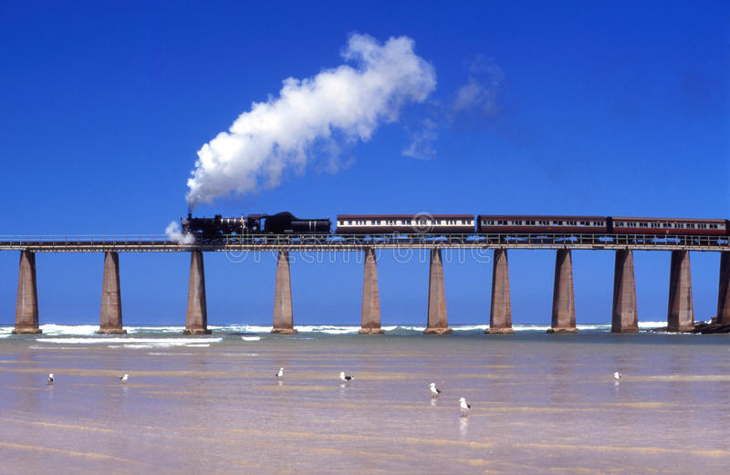 Steam train crossing Kaaimans River bridge South Africa. Former Outeniqua Choo-Tjoe crossing Kaaimans River Mouth at Wilderness on way to Garden Route town of stock image