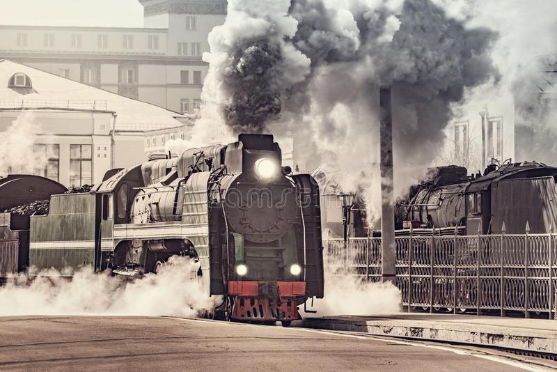 Steam train departs from the railway station stock photography