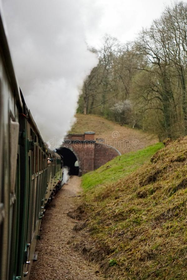 Steam train entering a tunnel royalty free stock photo