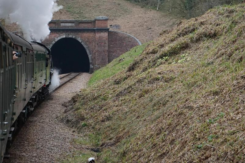Steam train entering a tunnel royalty free stock photography