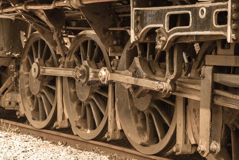 Steam Train Locomotive Wheels Closeup Vintage. Steam train locomotive closeup steel wheels at countryside station vintage sepia photo royalty free stock photo