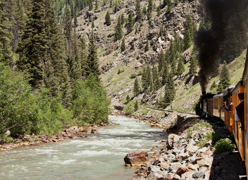 Steam train by river stock photography