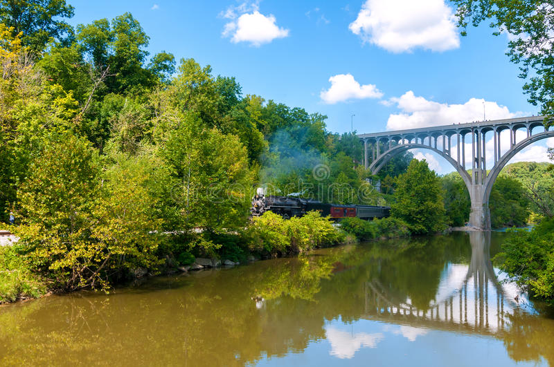 Steam train by river royalty free stock image