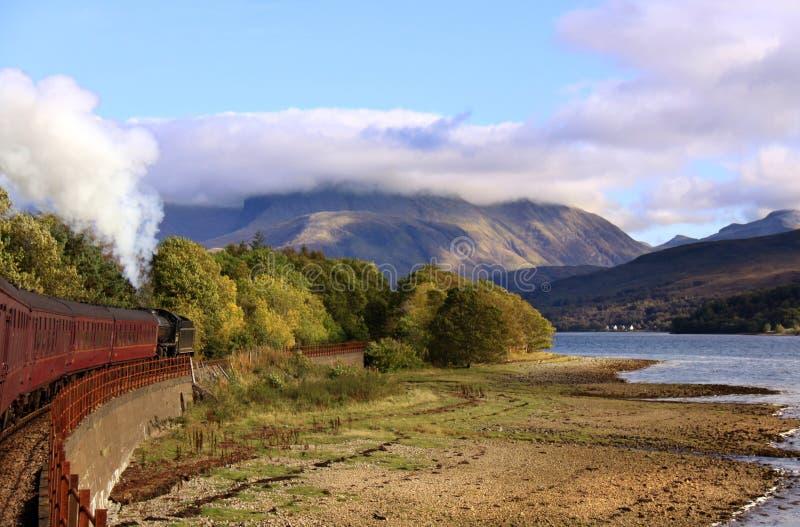Steam train travelling towards Ben Nevis, Scotland royalty free stock photos