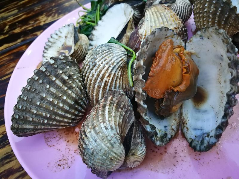 Steamed blanched clams with dipping sauce and spicy sauce that are famous of Thailand Street food stock photography
