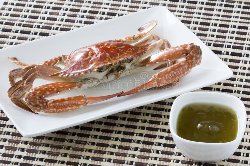 Steamed blue swimming crab and spicy sauce on a white Plate the wooden dish made of Japanese style bamboo royalty free stock photo