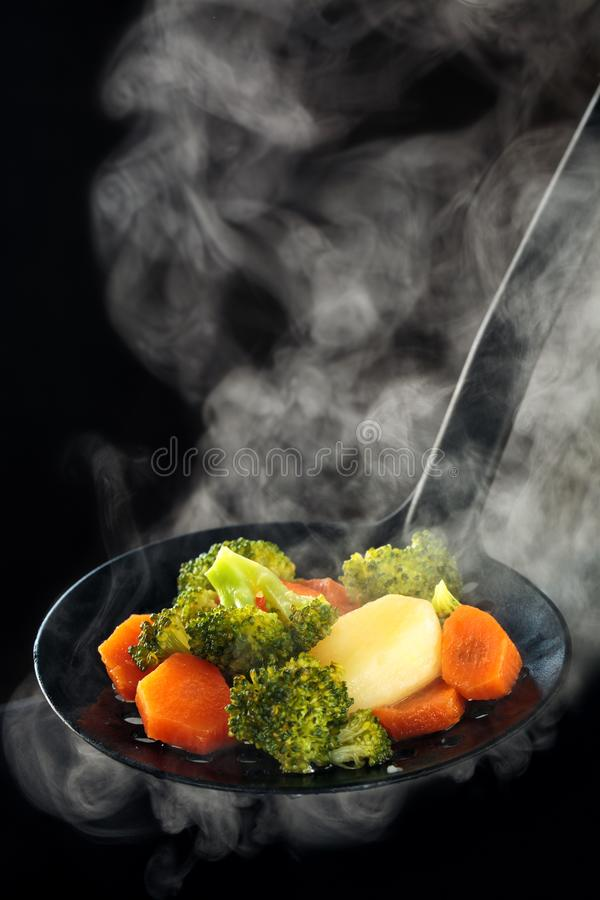 Steamed vegetables and steam. Steamed broccoli, potatoes and carrots with steam royalty free stock photography
