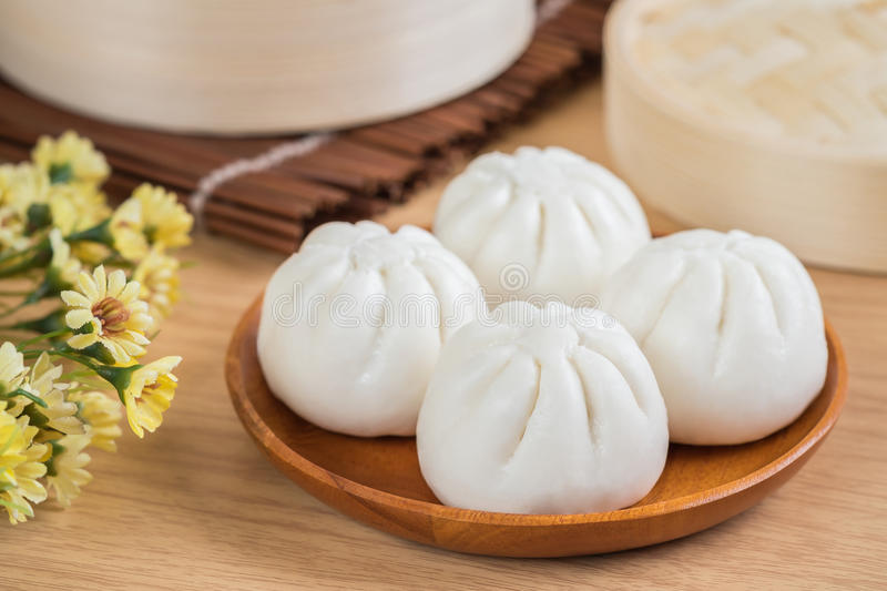 Steamed buns on wooden plate and bamboo basket stock photos