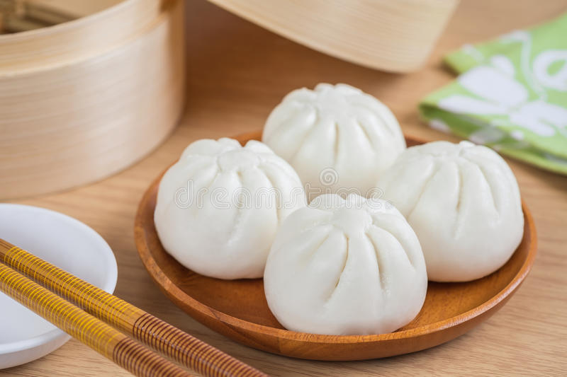 Steamed buns on wooden plate and bamboo steamer basket stock images