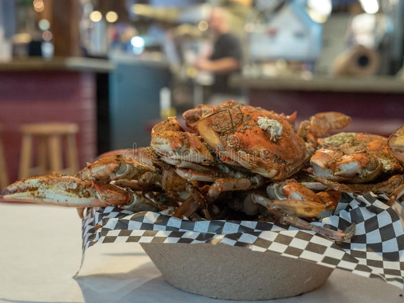 Steamed Chesapeake Bay blue crabs covered in seasoning sitting in paper bowl on paper covered table cloth royalty free stock photo