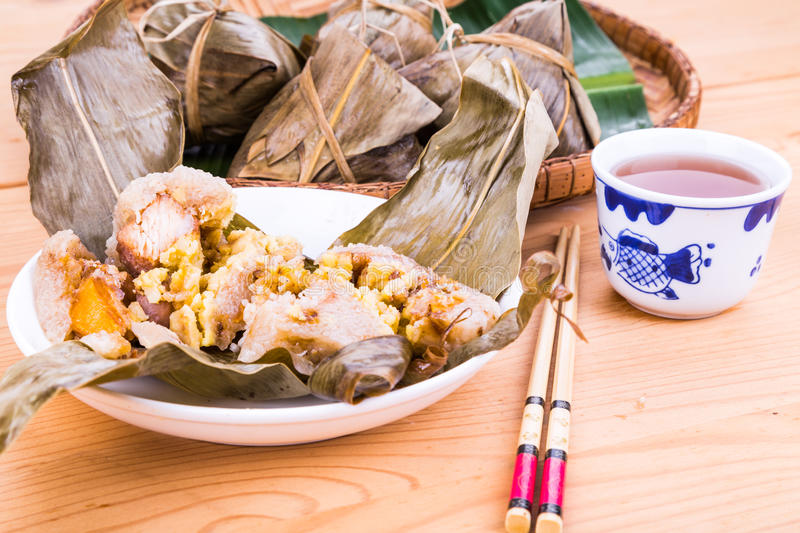 Steamed Chinese rice dumpling or zongzi served with oriental tea stock photos