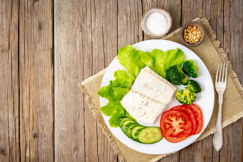 Steamed cod fish. Paleo, keto, fodmap healthy diet with vegetables on white plate on white table, side view. Steamed cod fish. Paleo, keto, fodmap healthy diet stock images