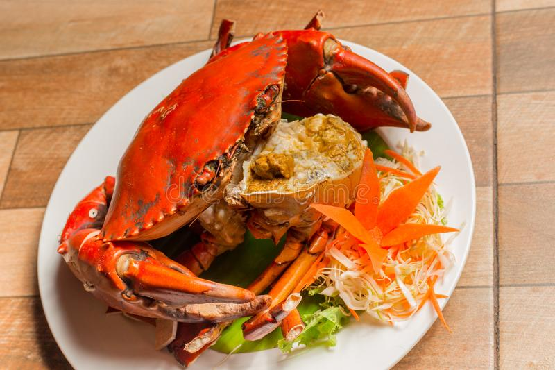 Steamed crab or Boiled crab fresh with crab`s spawn in white dish showing the delicious crab`s eggs inside its shell on wood table royalty free stock photo