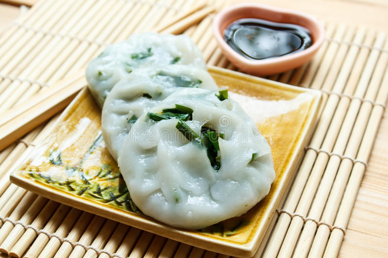 Steamed dumpling stuffed with garlic chives (Chinese chives). Steamed dumpling stuffed with garlic chives served with sweet black sauce royalty free stock photos