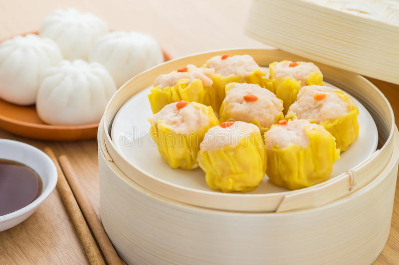 Steamed dumplings in bamboo steamer basket and steamed bun on pl stock photos