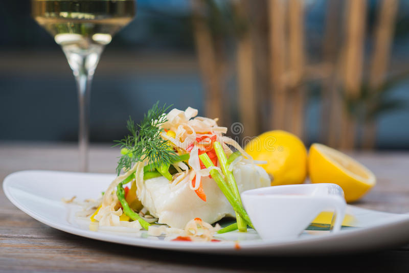 Steamed fillet of sea bass. Serving of steamed sea bass fillet on a plate in a restaurant, on a wooden table with white wine and decor stock photo