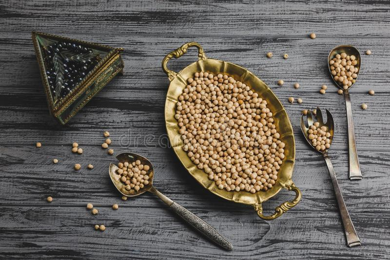 Steamed gold chickpeas in bowl with vintage spoons, tasty vegan food stock photography