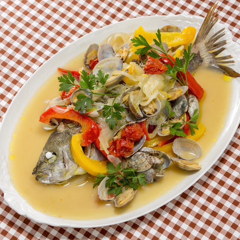 Steamed grouper fish with clams, chili and herbs on white platte stock image