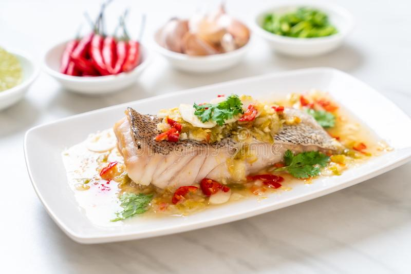 Steamed Grouper Fish Fillet with Chili Lime Sauce in lime dressing. Asian food style royalty free stock photography