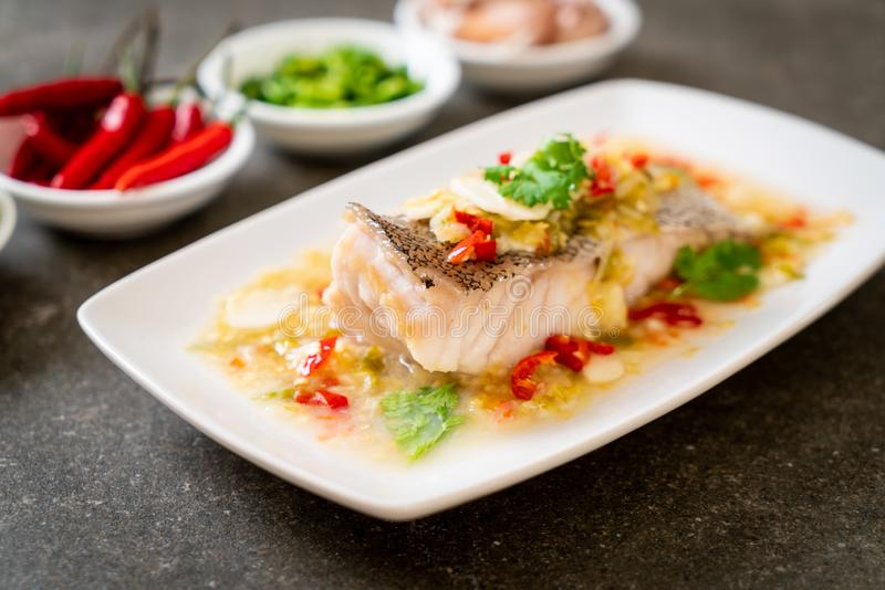 Steamed Grouper Fish Fillet with Chili Lime Sauce in lime dressing. Asian food style stock photo