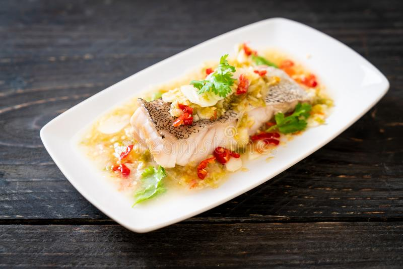 Steamed Grouper Fish Fillet with Chili Lime Sauce in lime dressing. Asian food style stock photos