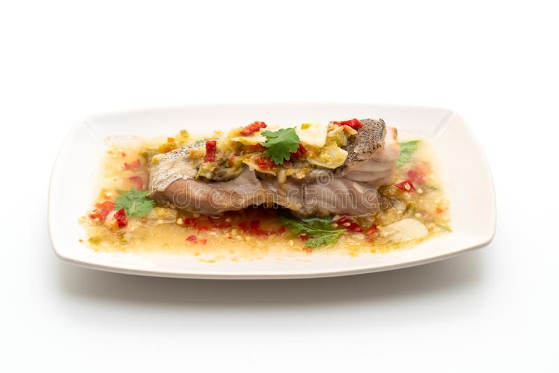 Steamed Grouper Fish Fillet with Chili Lime Sauce in lime dressing. Isolated on white background royalty free stock image