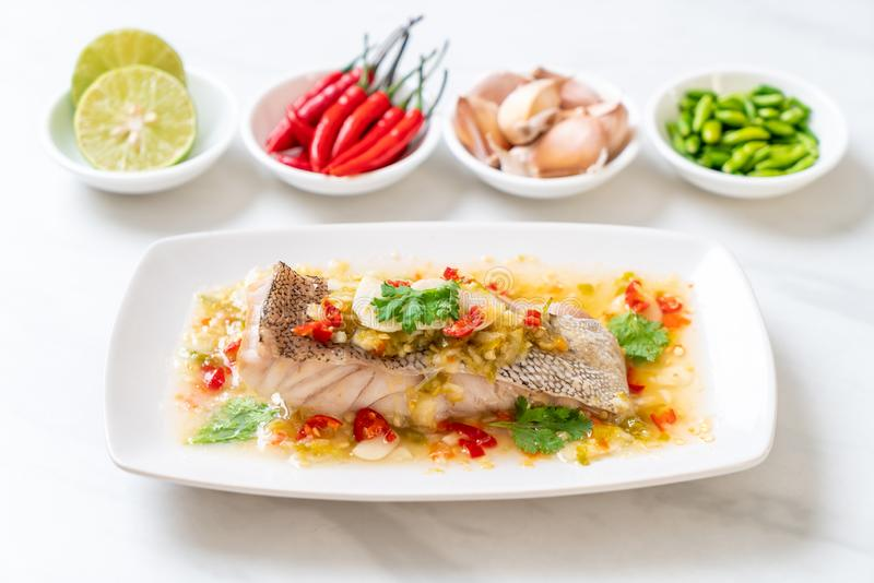 Steamed Grouper Fish Fillet with Chili Lime Sauce in lime dressing. Asian food style royalty free stock photo