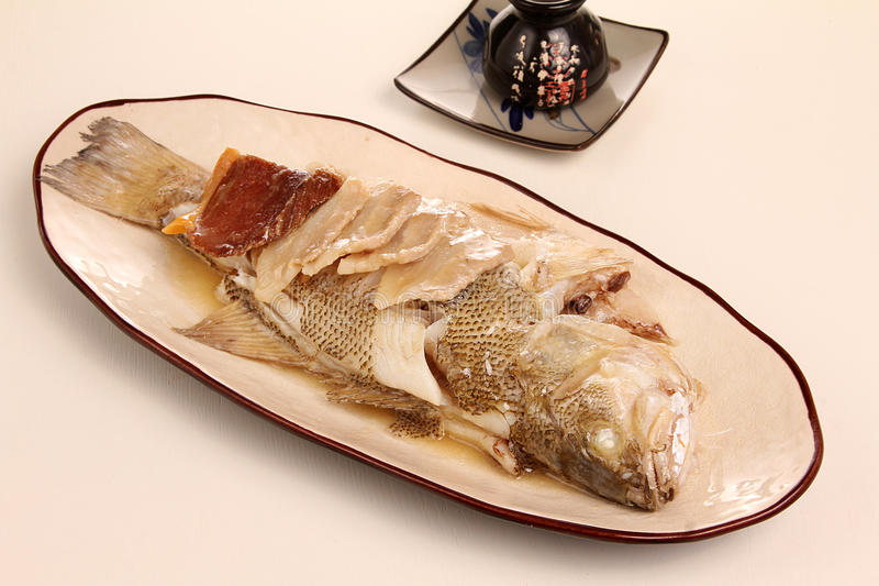 Steamed grouper in Japanese style on plate in restaurant royalty free stock images