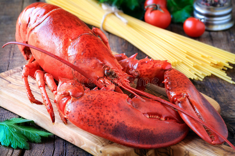 Steamed lobster. Delicious steamed lobster on wooden cutting board and spaghetti at the background stock photography