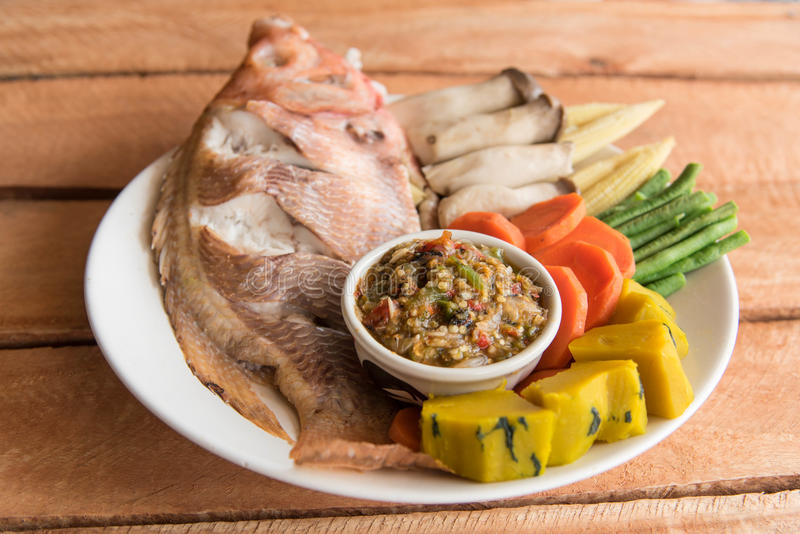 Steamed Nile tilapia fish and vegetables, served with sauce royalty free stock image