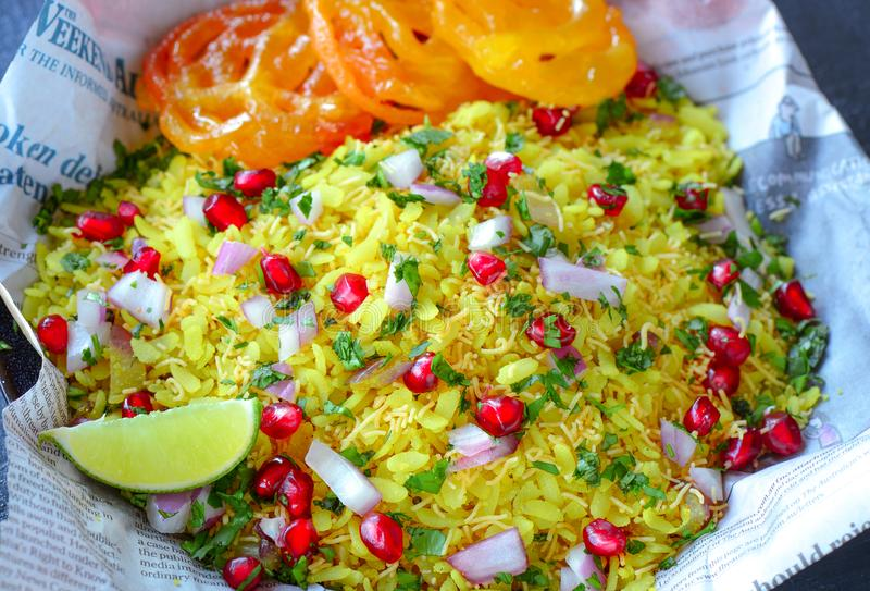Indian street food breakfast poha jalebi. Steamed rice flakes served with pomegranate seeds,onions,dash of lime in a newspaper plate.Served along with sweet stock photo