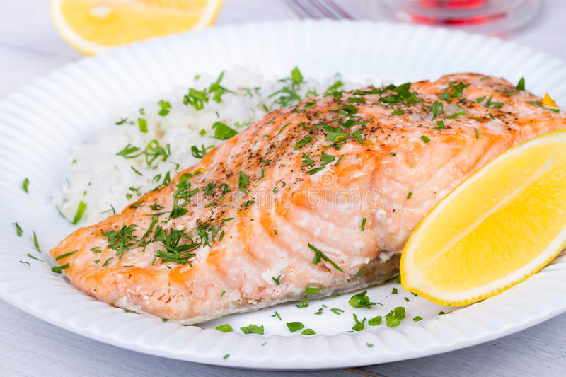 Steamed salmon with fresh herbs and lemon. Rice as a garnish. royalty free stock image