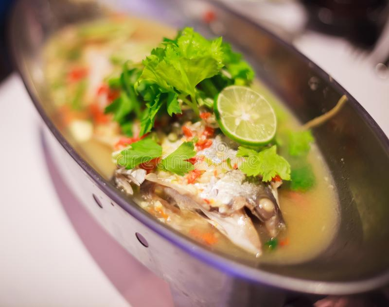 Steamed snapper pacific ocean perch, sea bass, ruby perch hotpot in spicy lemon sauce in Asian Thai Style. Healthy cooking royalty free stock photo