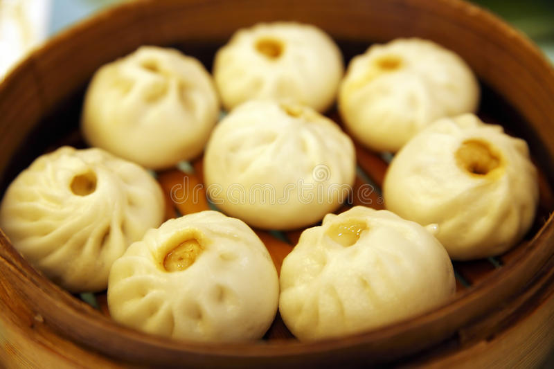 Steamed stuffed bun. One of Chinese Cuisine. Baozi are steamed buns filled with ground meat and cabbage. Main focus on the dumpling at the front stock images