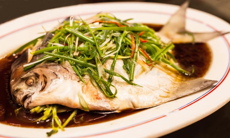 Steamed White Silver Pomfret with spring onion, chili and soy sauce stock photo