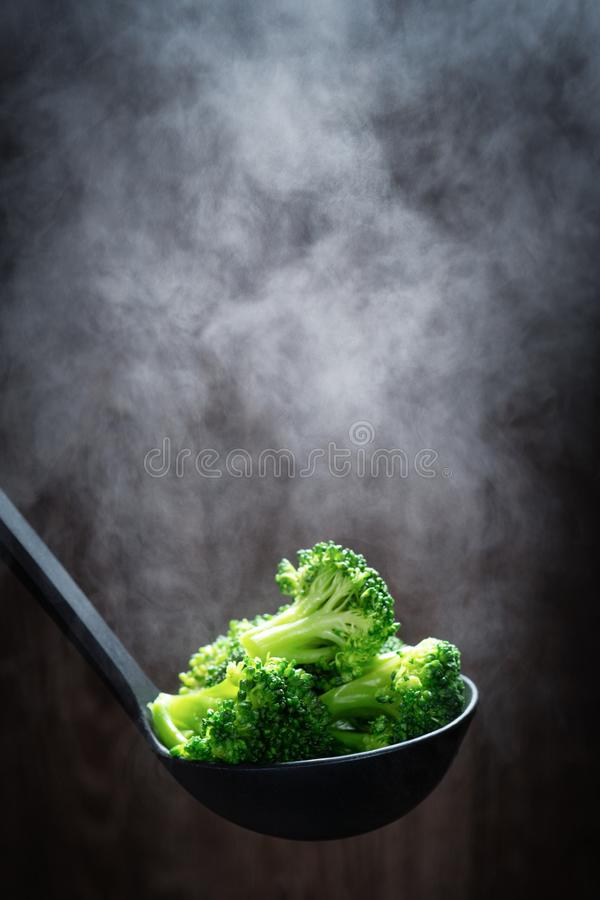 Steaming broccoli in black kitchen spoon stock photography