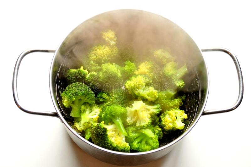 Steaming broccoli in an inox pot royalty free stock images
