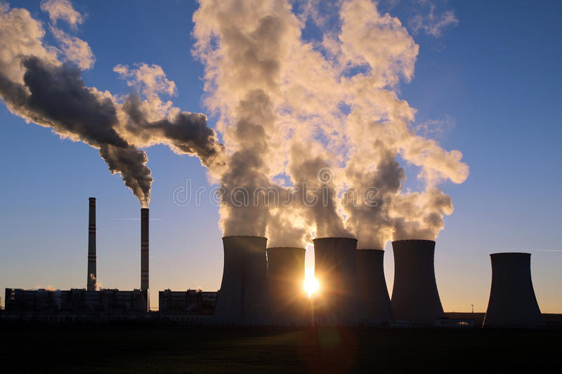 Steaming cooling towers of coal power plant against the sun. Smoking cooling towers of coal power plant against the sun stock images