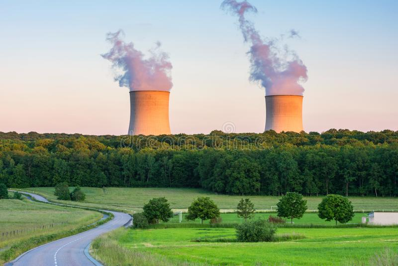 Steaming Cooling Towers at Nuclear Power Plant around Sunset. Steaming Cooling Towers at Cattenom Nuclear Power Plant in Cattenom, Northeastern France. Captured stock photo