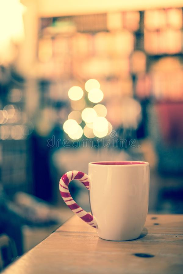 Steaming cup of thee on a wooden table, christmas time, blurry background. White cup of tea is standing on a wooden table. Steam and blurry background whit royalty free stock photos