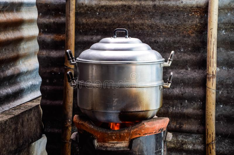 Steaming food in cooking pot on a charcoal stove in kitchen on old zinc background stock photos