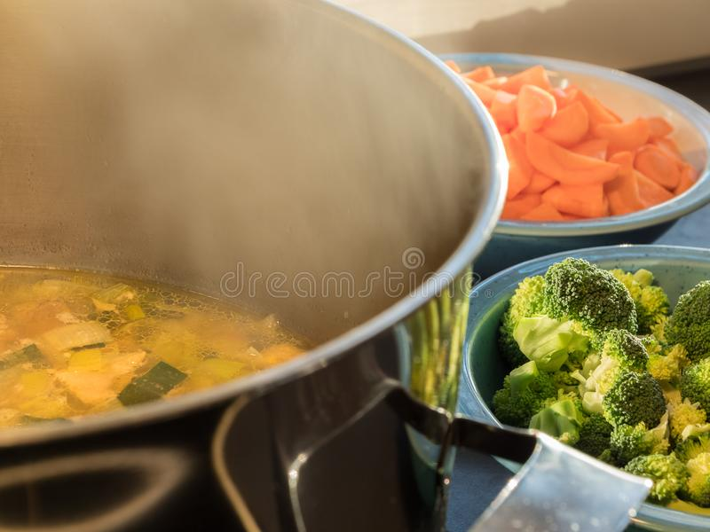Steaming soup pot with broccoli and carrots stock photos