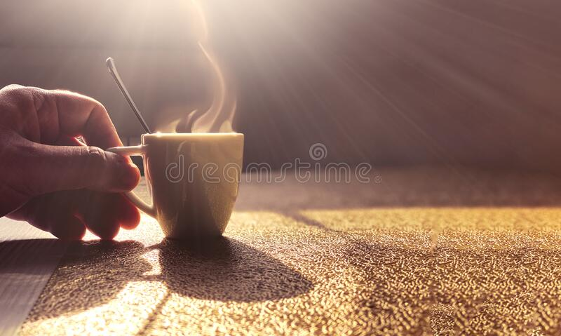 A steaming white ceramic cup containing coffee on a table lit by the light of the dawn sun. A male hand holds the cup by the. Handle. Morning coffee break stock photo